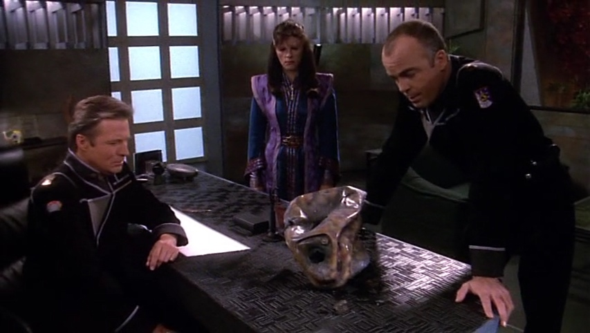 Kosh's ruined helmet on Sheridan's desk, surrounded by Sheridan, Delenn and Garibaldi.